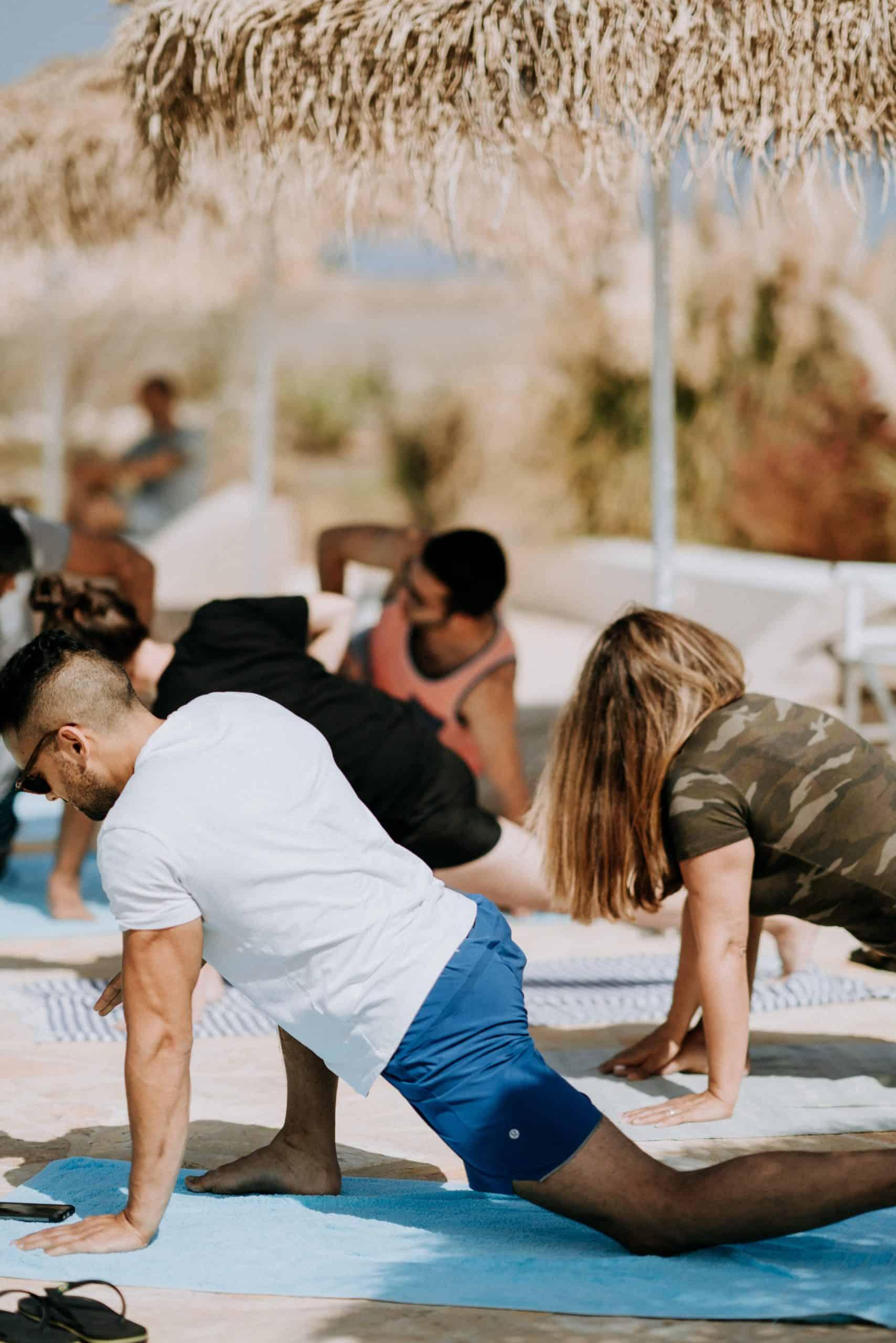 Annie Spratt Unsplash image of Yoga retreat outdoors men and women in asana