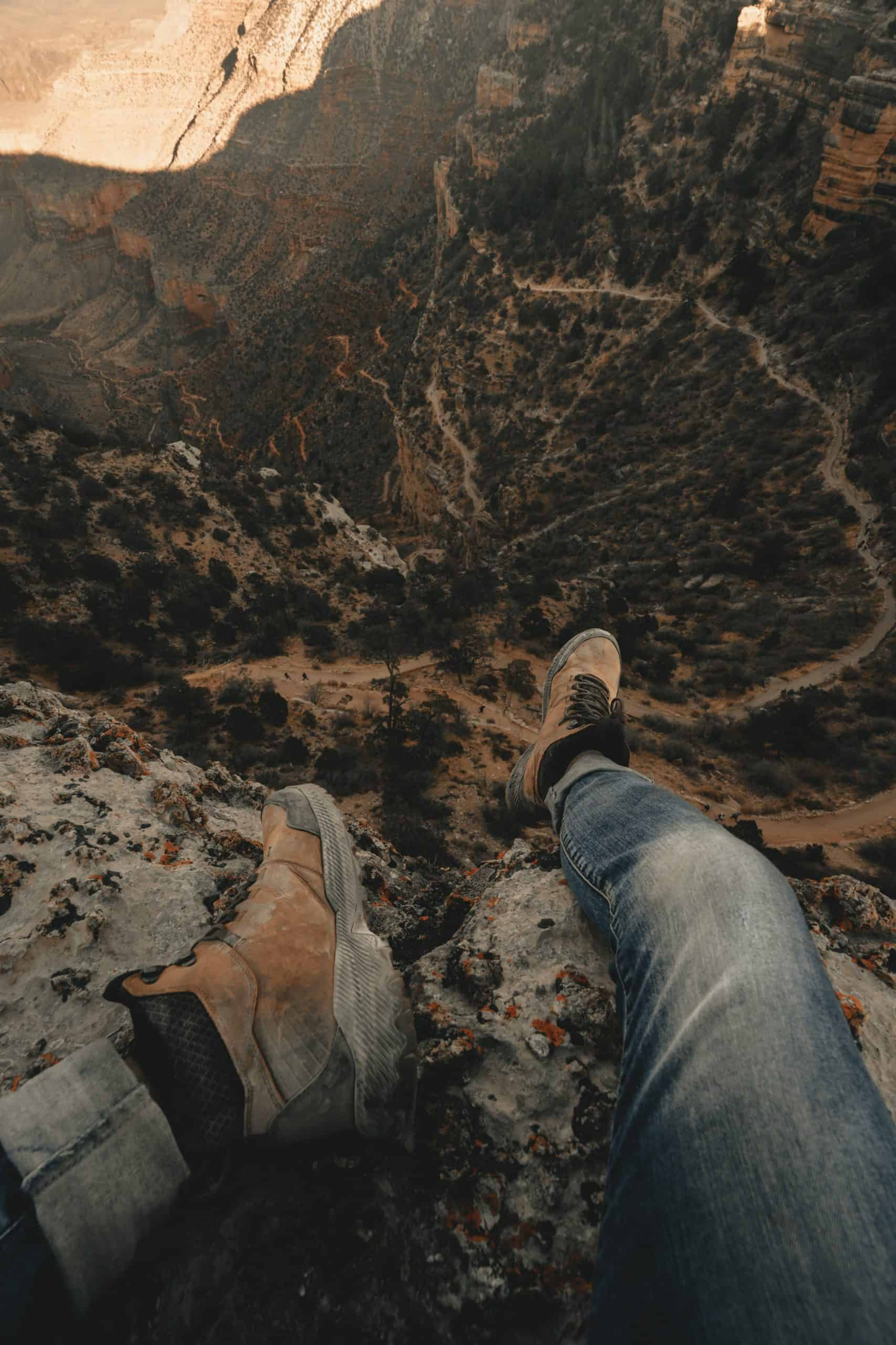 Clay Banks image Unsplash hanging over the canyon edge with merrell boots on