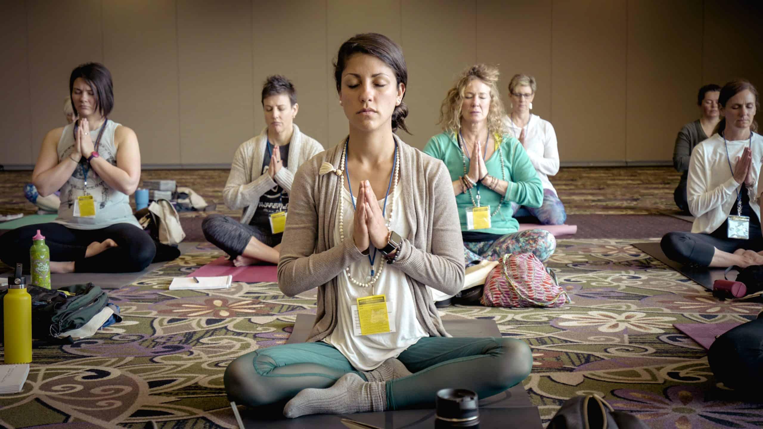 Photo by Erik Brolin on Unsplash of Women in Meditation pose Yoga class