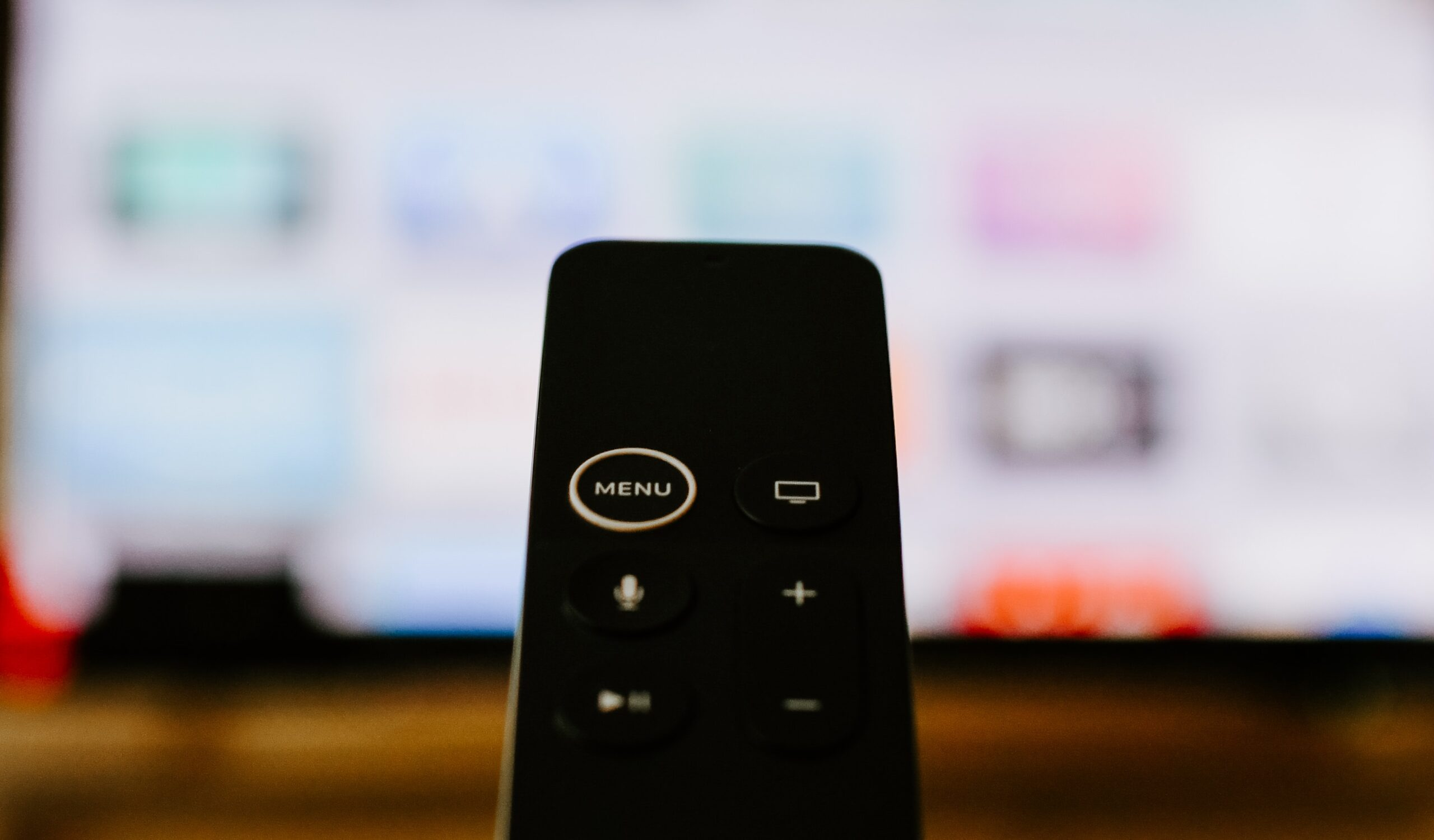 kelly-sikkema-Apple TV4k remote and screen in background-unsplash