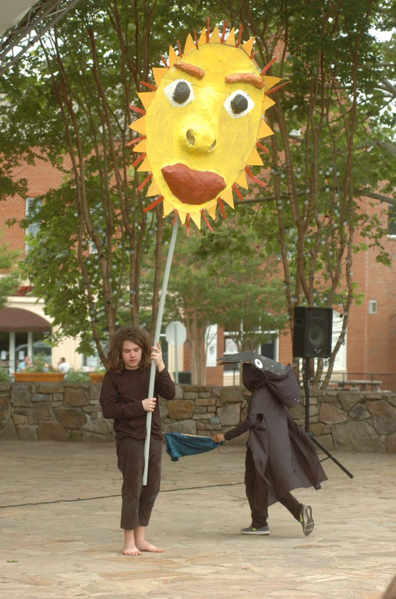 Sol Ramirez puppetiering a large sun puppet with puppeteer Tarin pipkins in a crow mask flying around