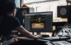 Guitarist with Positive Grid software on large computer screen