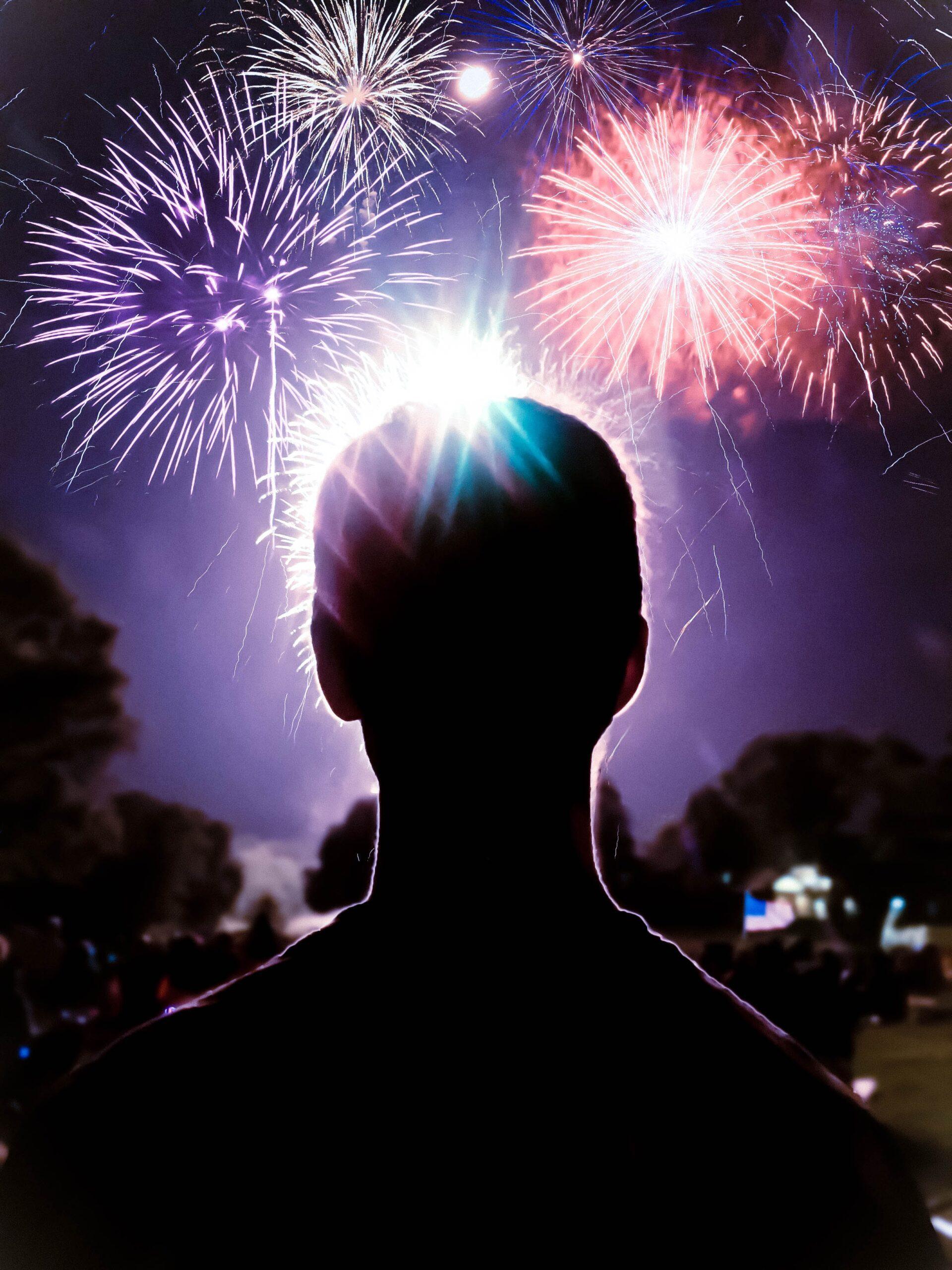 spenser-sembrat-man in foreground looking at fireworks display-unsplash