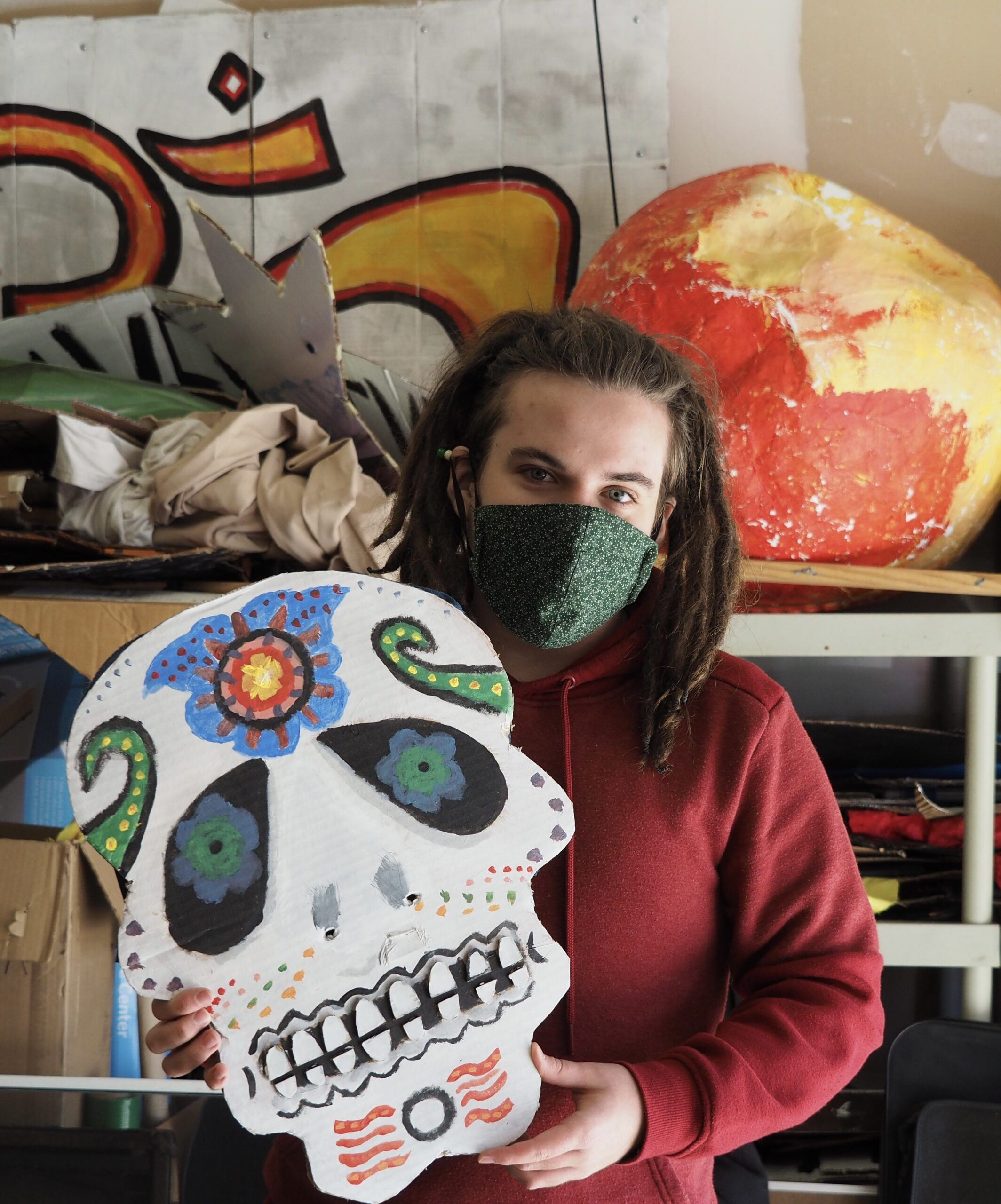 Sol Ramirez with Covid Mask holding skeleton Head mask in workshop by Aeon Schmoock