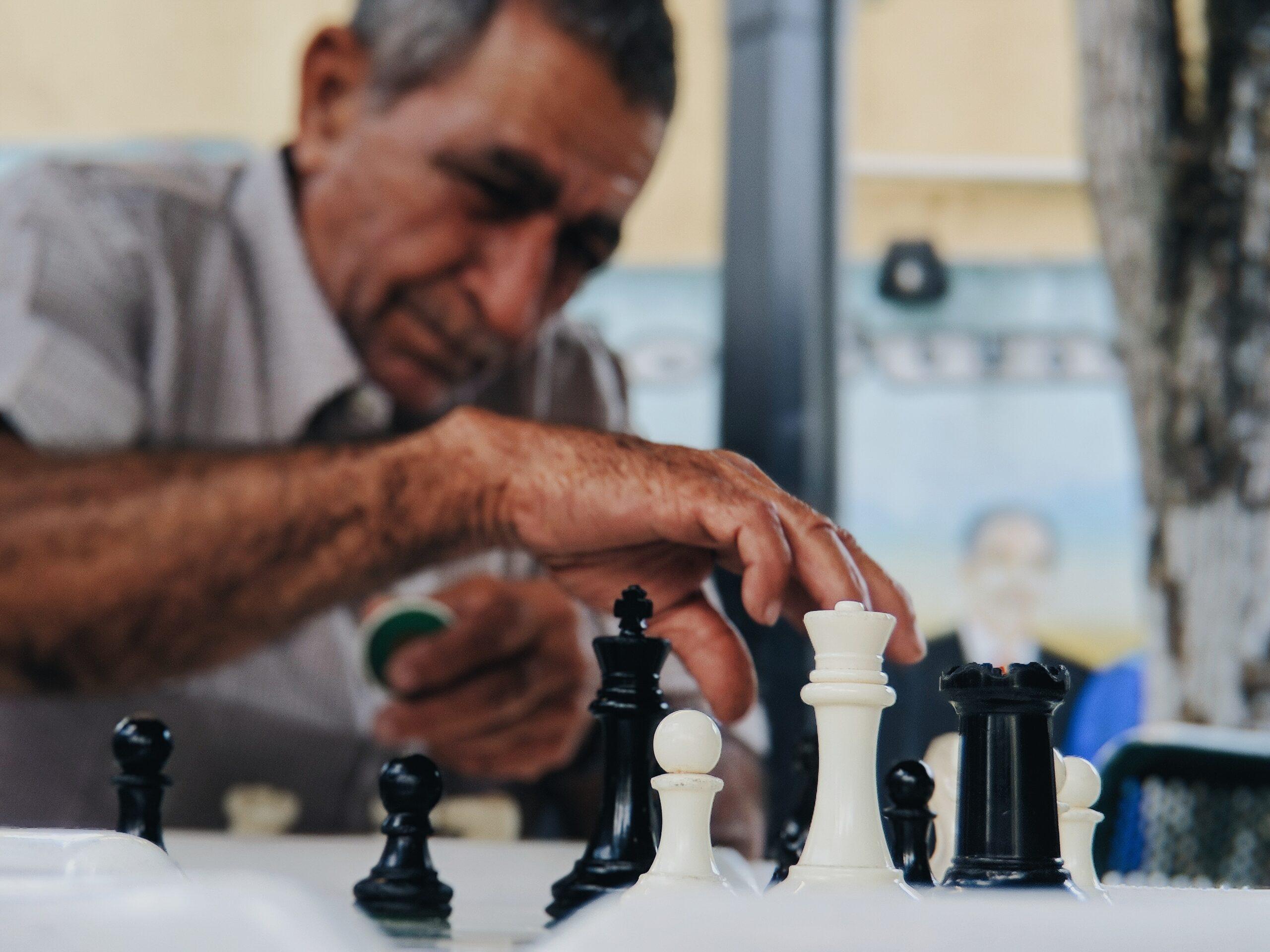juno-jo-Man outdoor park chess board moving piece-unsplash (1