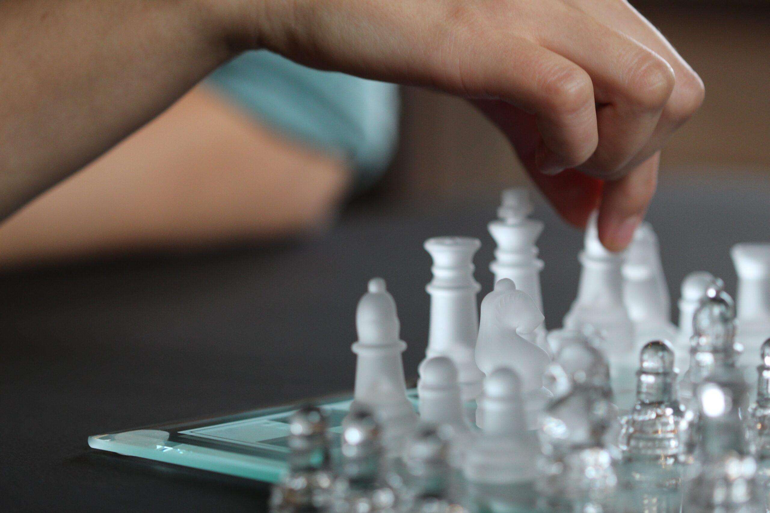 anne-nygard-Glass chess set hand in closeup moving piece-unsplash