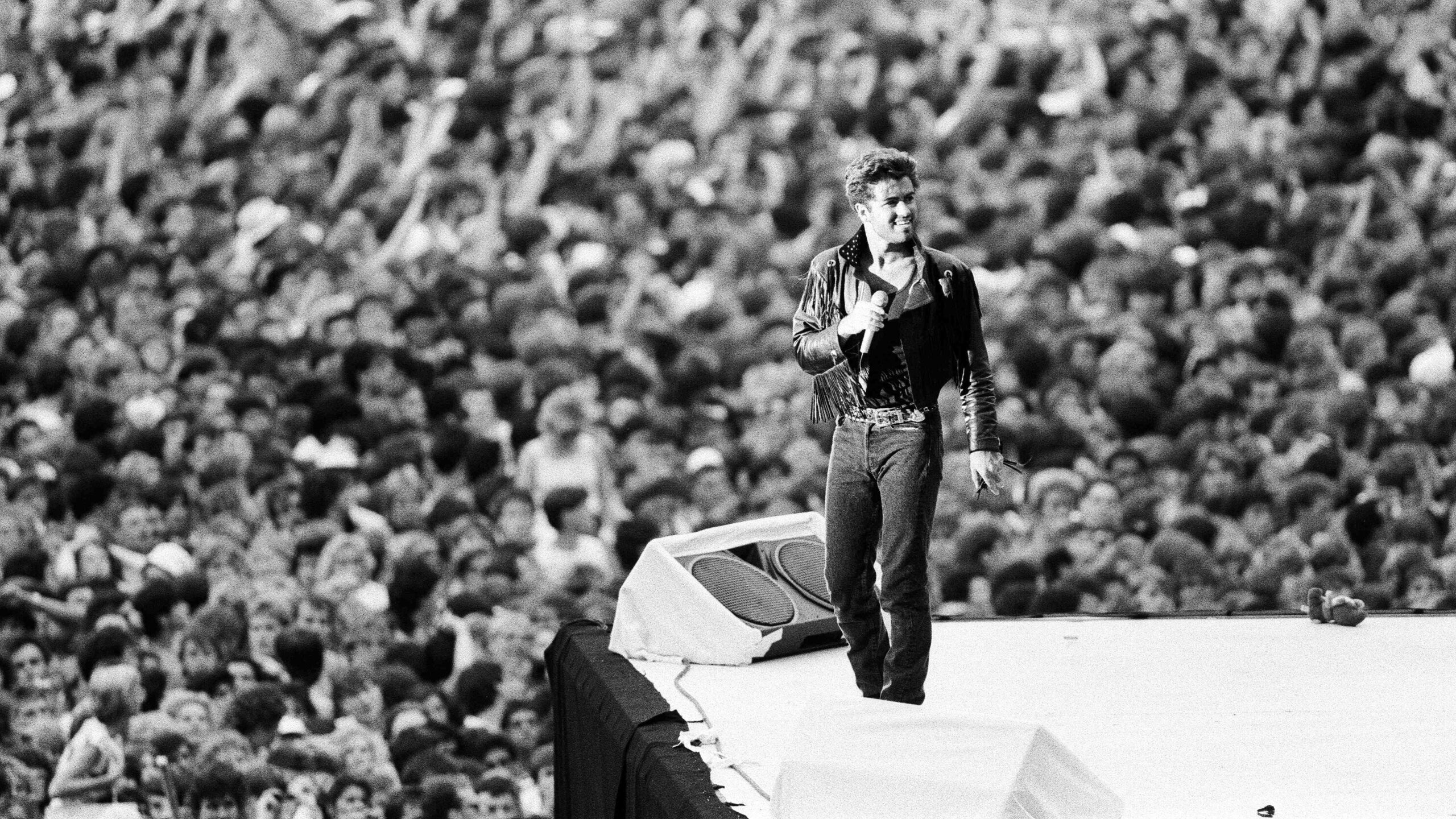 George Michael on stage with crowd behind
