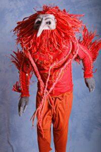 -Shaman in bird mask and redshirt orange pants- by Hrustall photographer on Unsplash