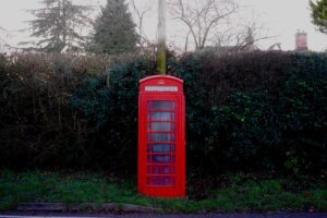 jack-bassingthwaighte-UK red phone box at pole backed up by hedgrow-unsplash