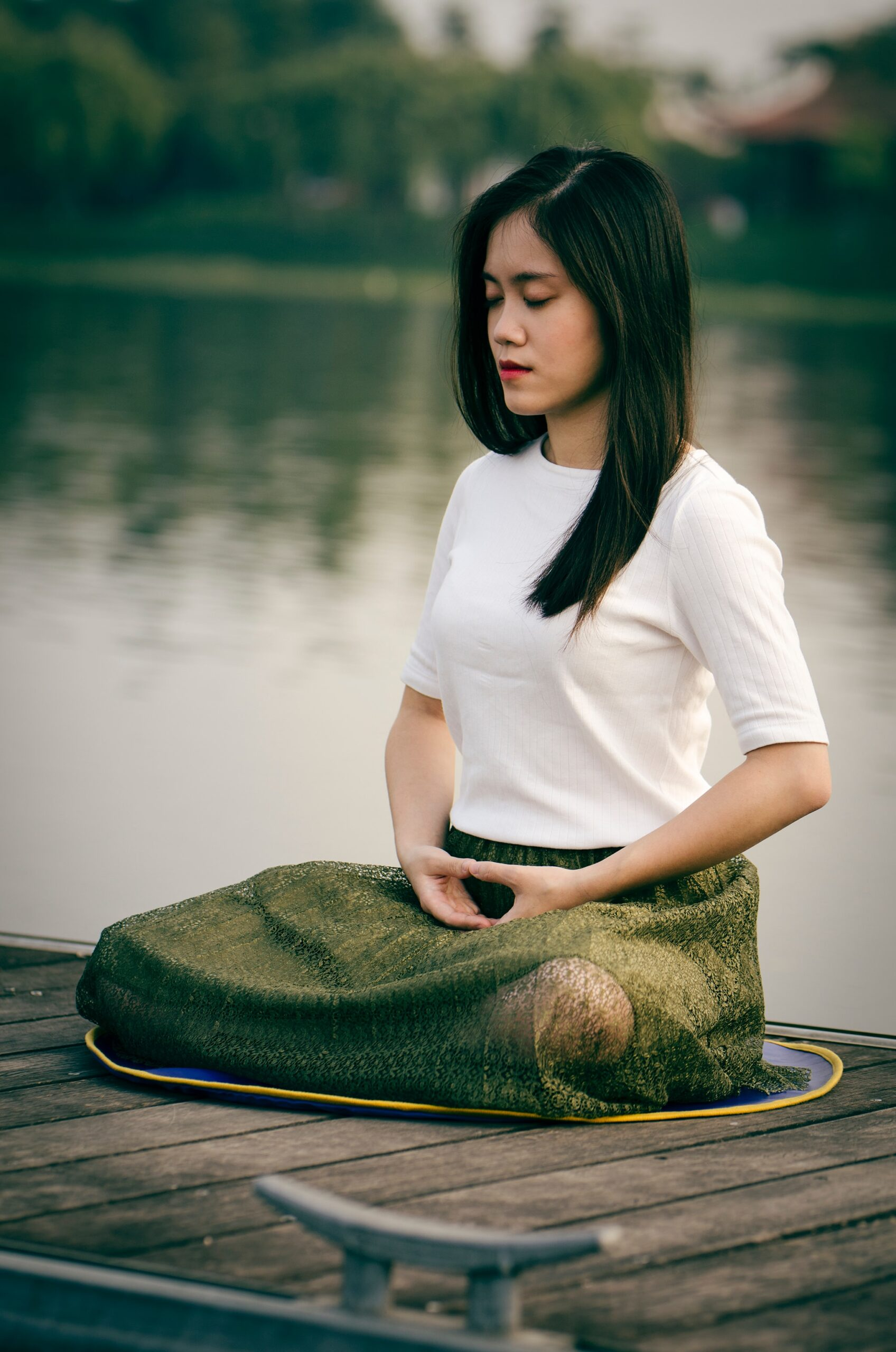 woman on lake dock meditating Le Minh Phuong photographer from Unsplah.