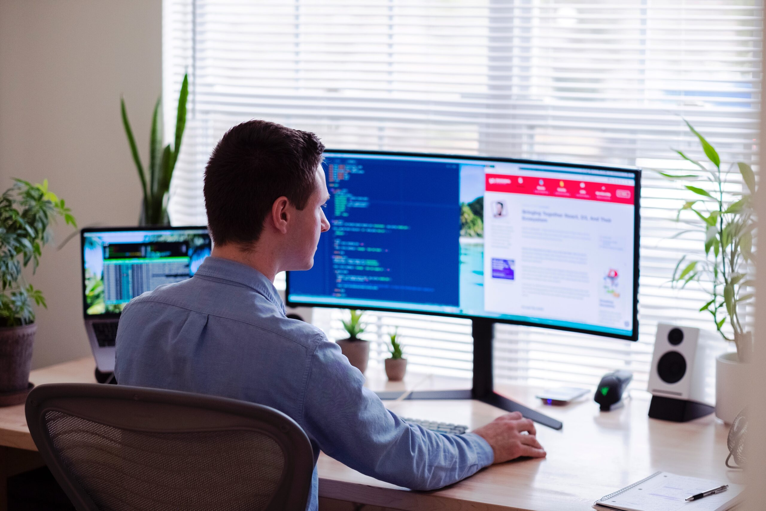 luke-peters-web developer at desk with two large displays-