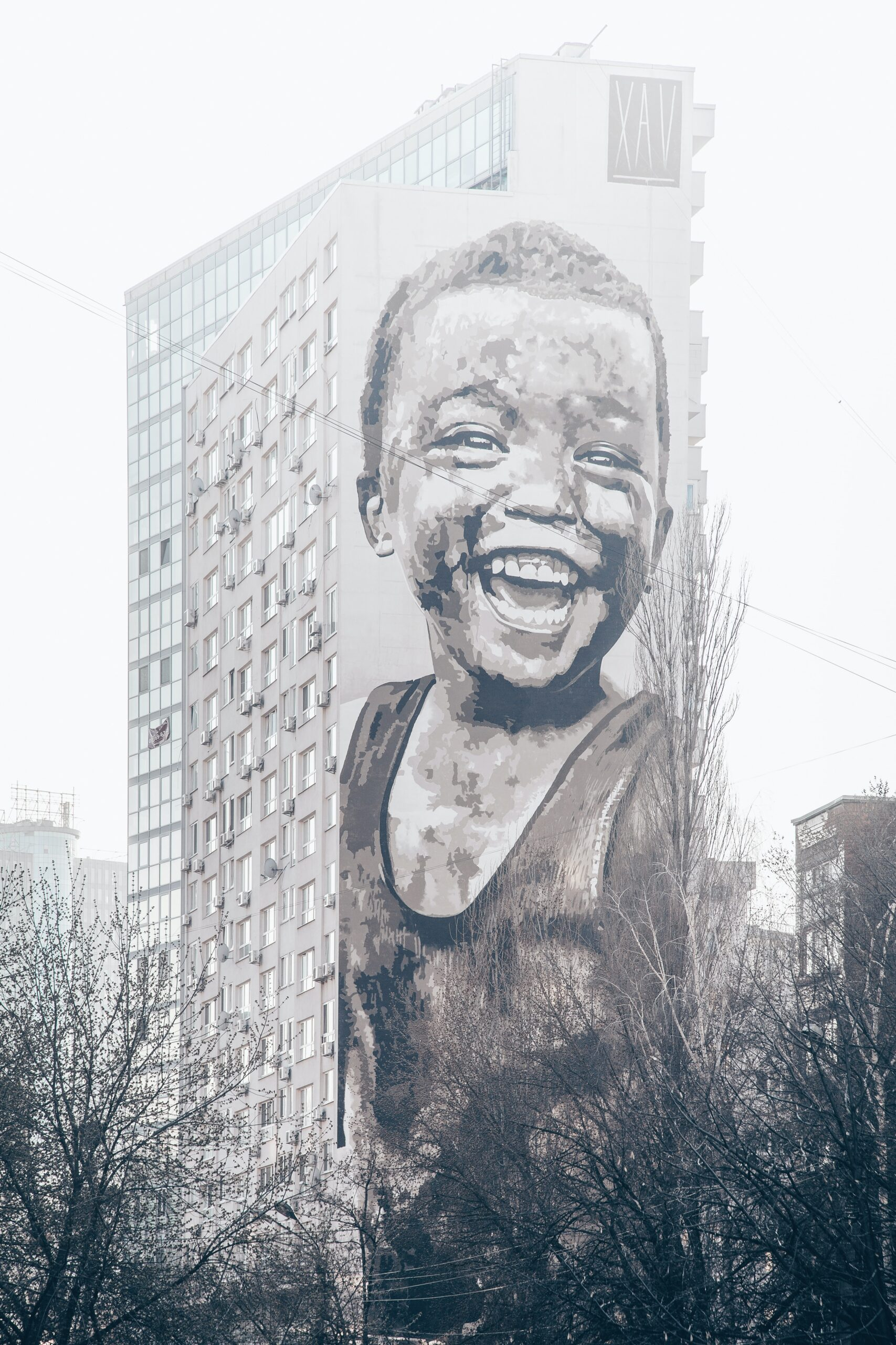 Mural on side of building of young boy smiling by Marja Murd from Unsplash