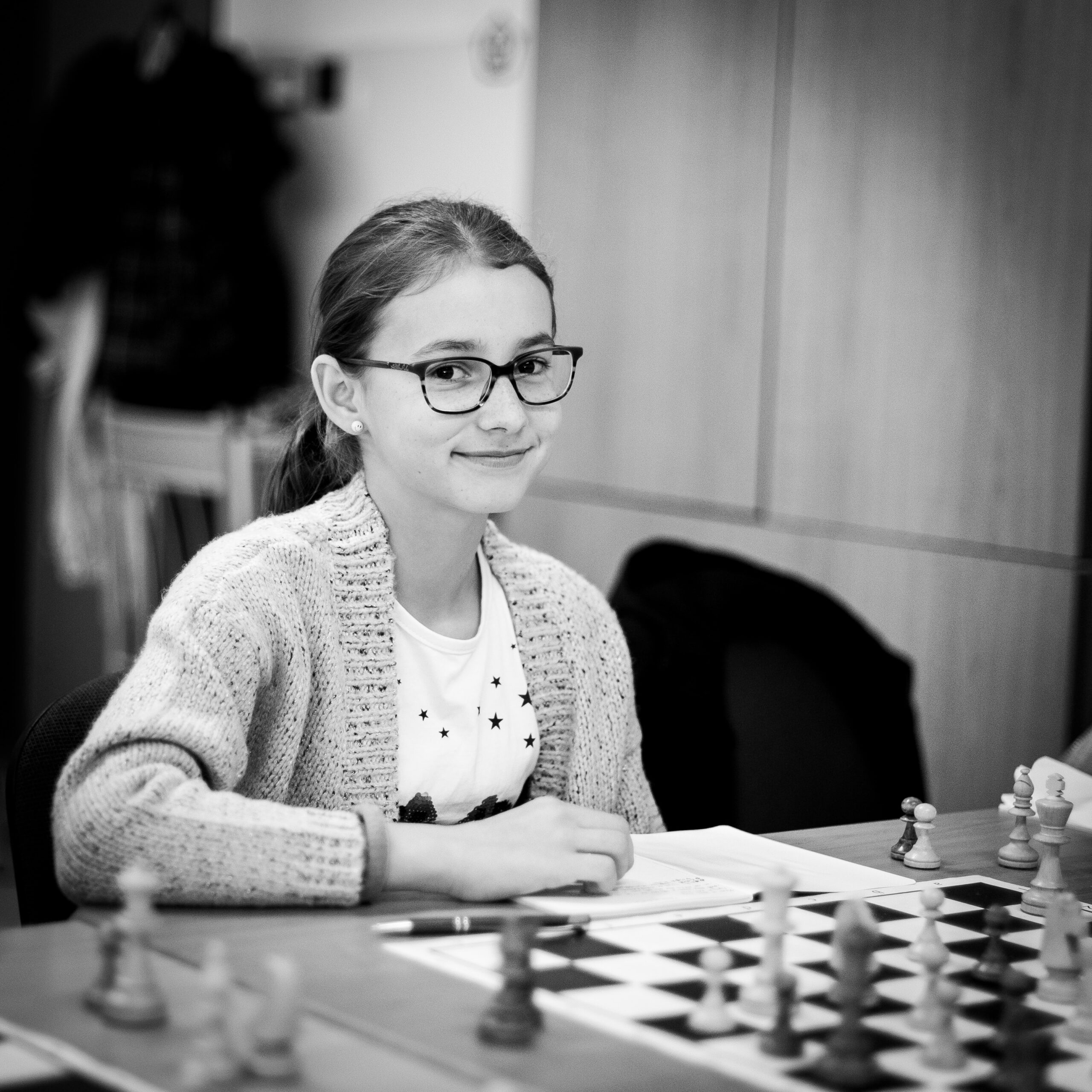 michal-vrba-young lady sitting at chess table-unsplash (1)