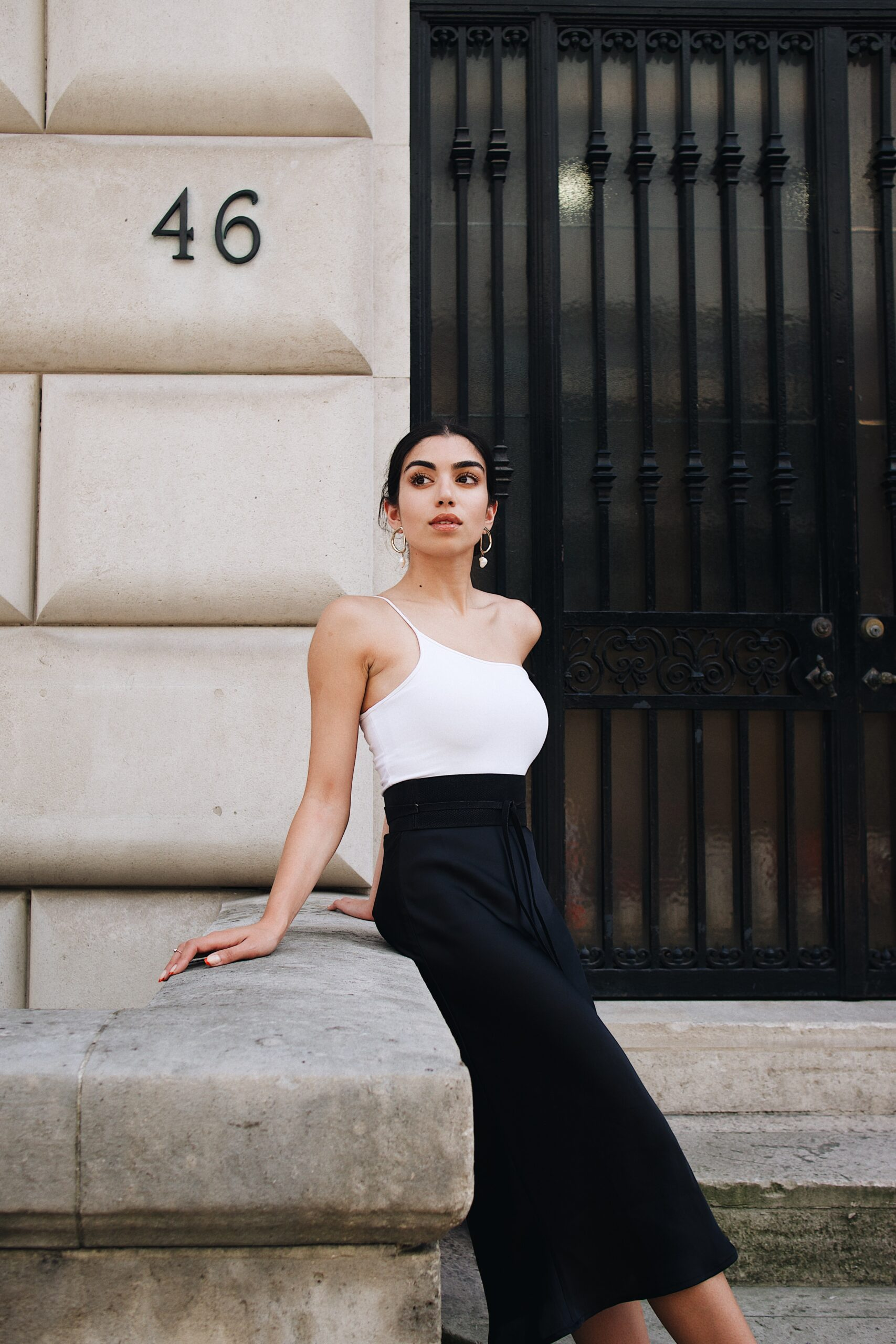 Connie-hiles-Woman in a white camisole and black dress leaning against rail of building entrance-unsplash
