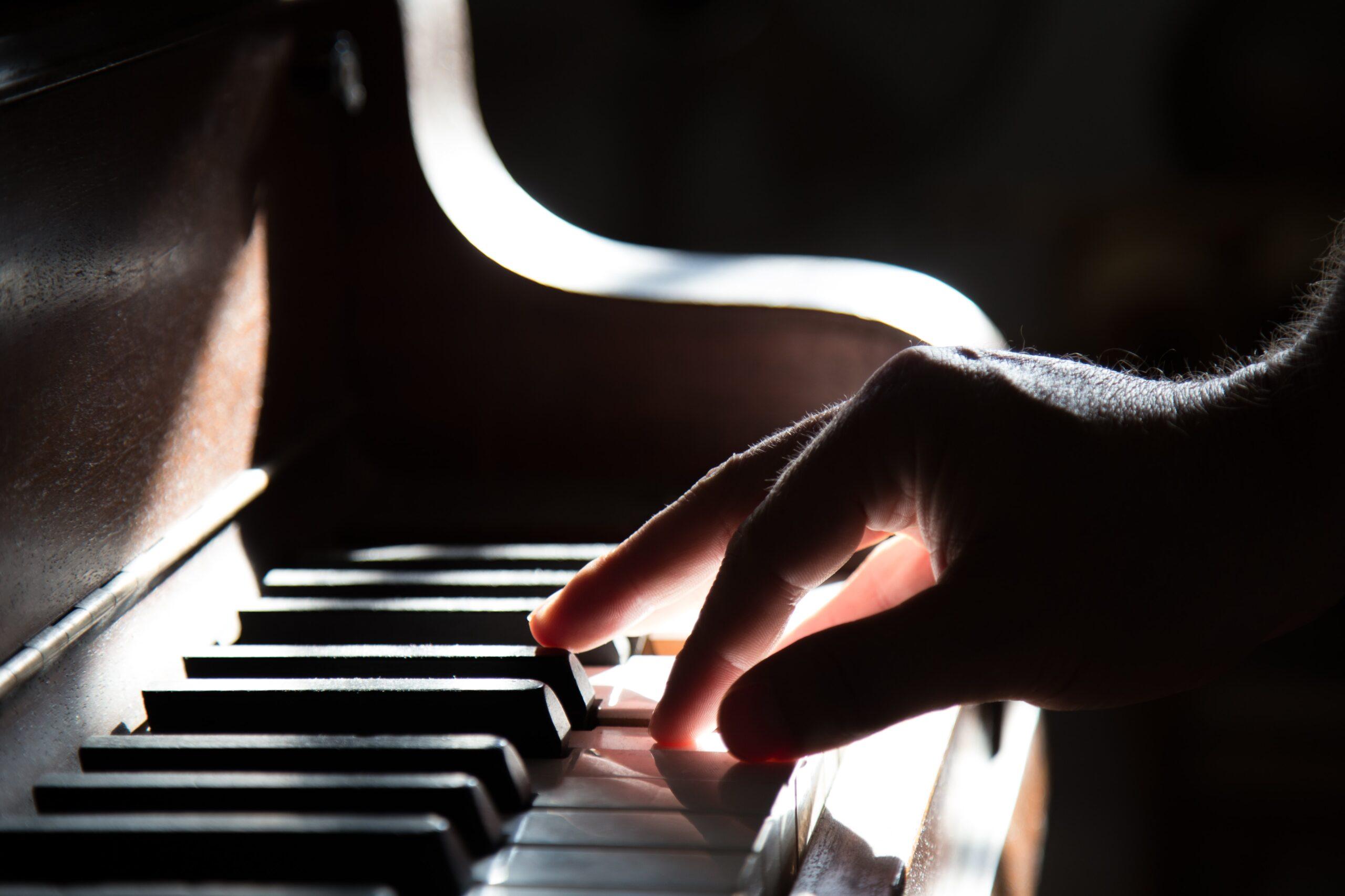 tadas-mikuckis-Close up of Right hand on piano keys-unsplash