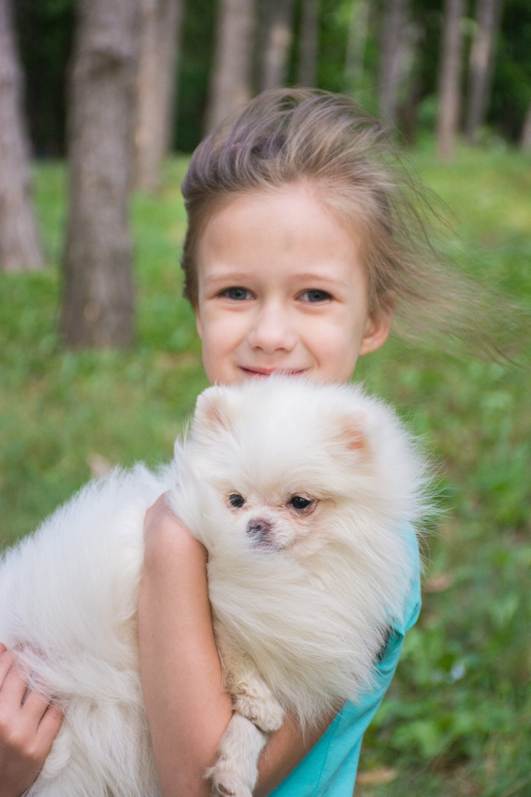 Girl holding pomeranian dog in the wind