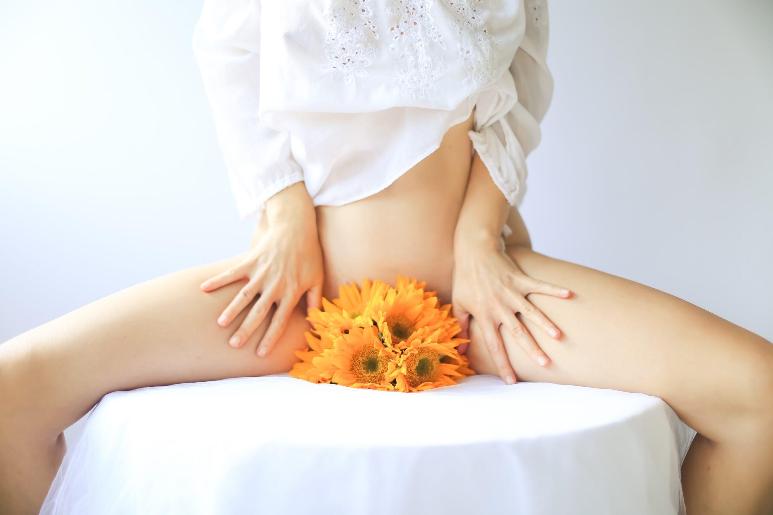 ava-sol-Woman with orange daisy blossoms held between legs -unsplash