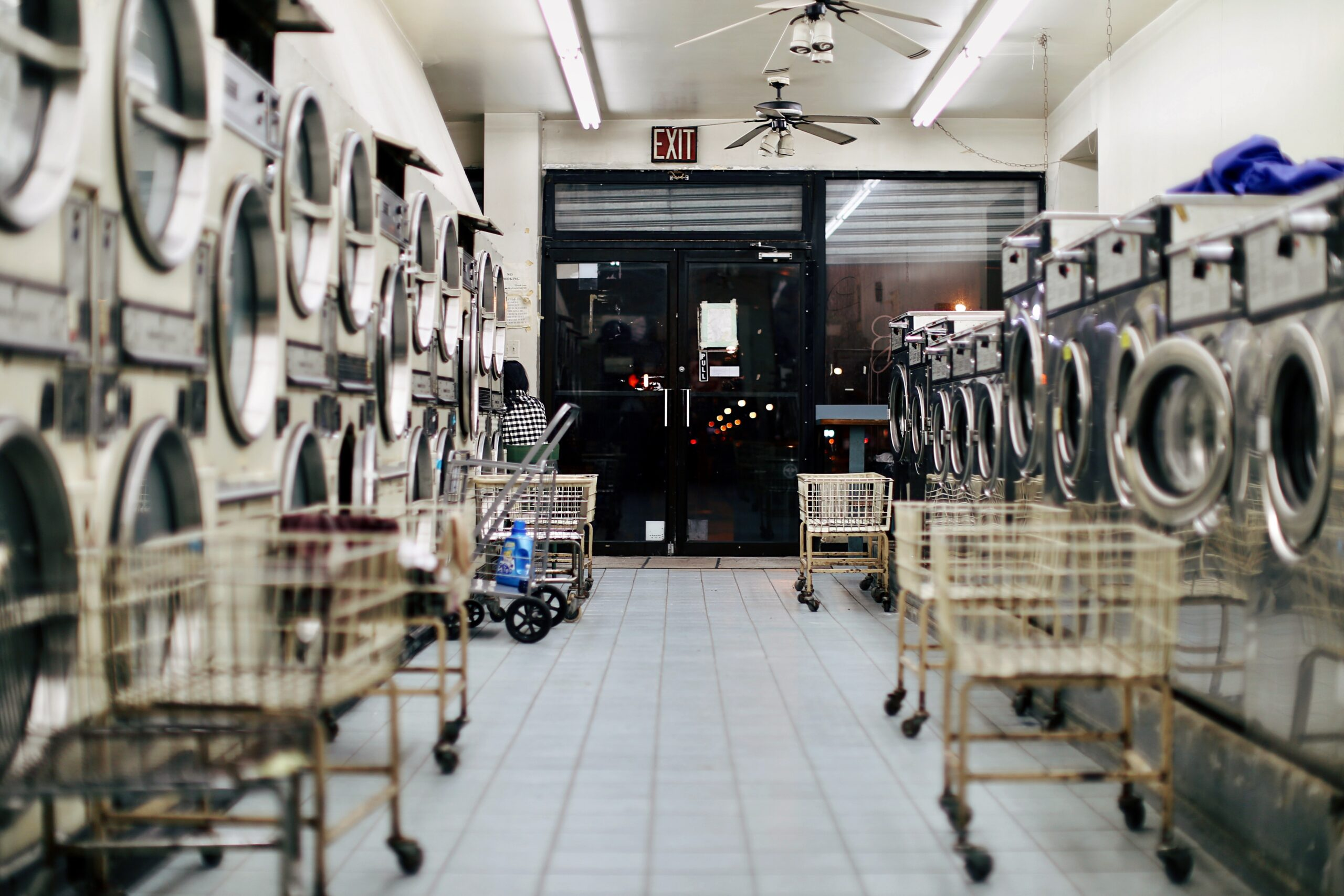 bianca-jordan-Laundry Mat lane with stacked machines on either side and carts lined up against machines-unsplash