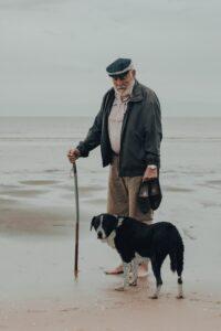 gaspar-manuel-zaldo-Older bearded gentleman with hat grey coat and dog at side-unsplash