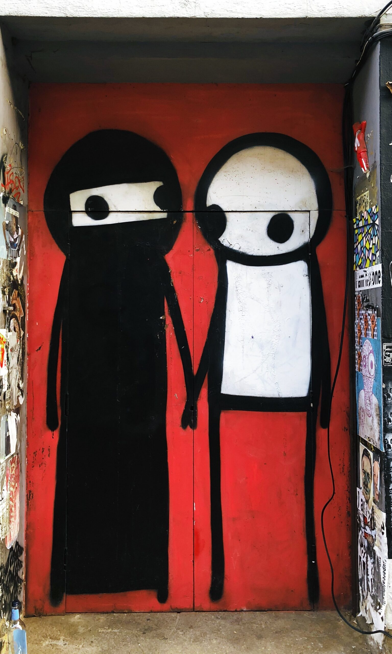Two stick figures holding hands graffiti red background by Jon Tyson from Unsplash