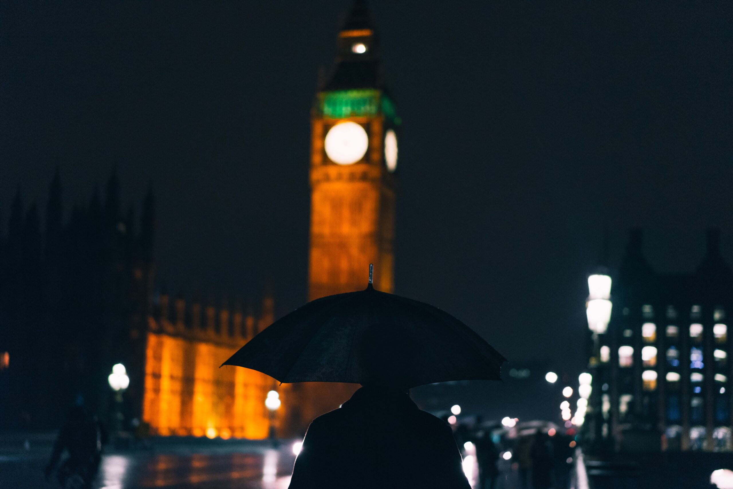 kid-circus-Man with black umbrella walking at night near tower of London-unsplash