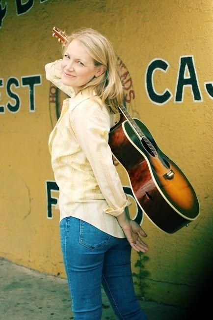 Kelly Willis with Acoustic Guitar strung over her back