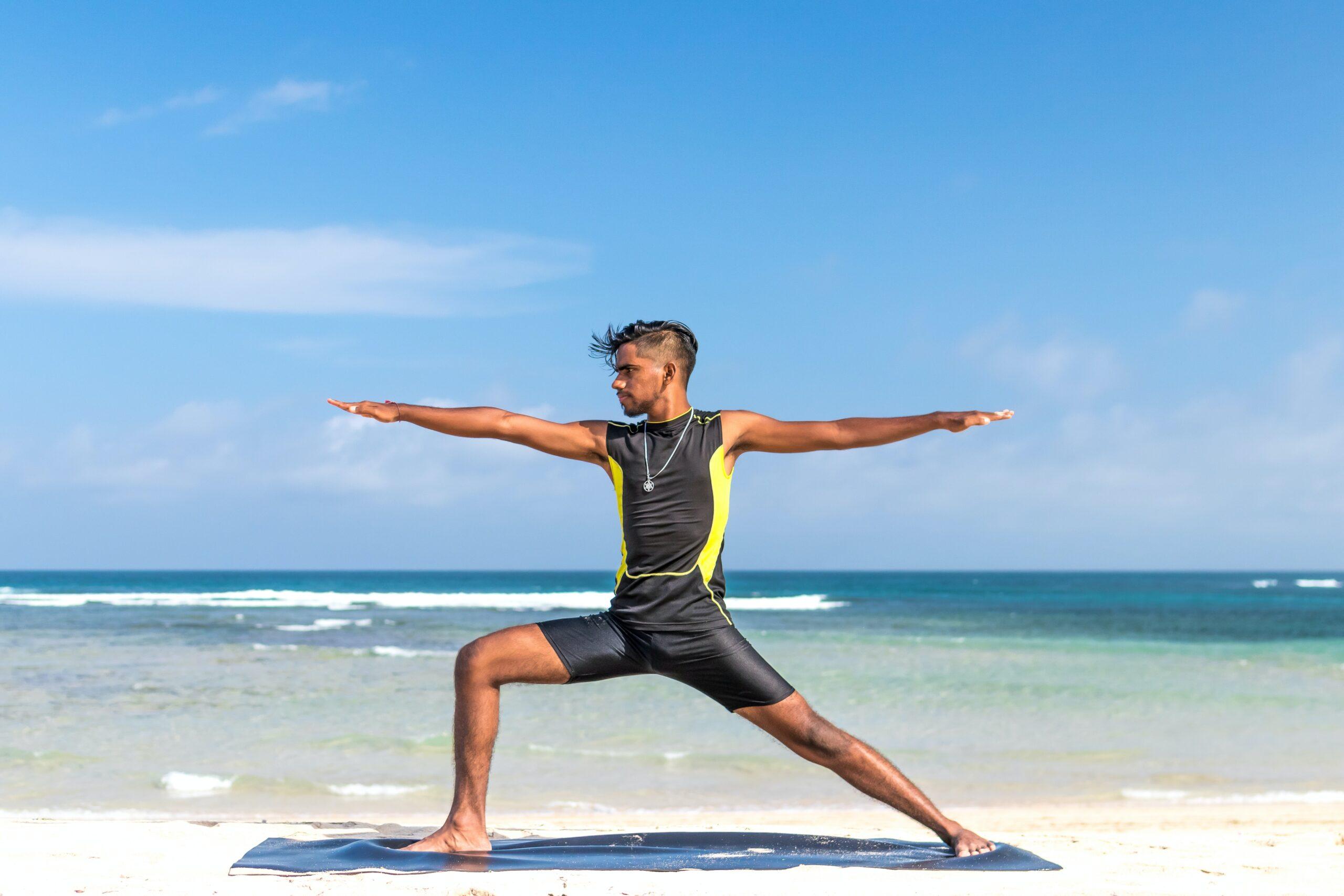 artem-beliaikin-Man on beach in warrior asana-unsplash