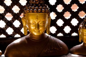 jeff-ackley-Golden Buddha head with Rosewood lattice background-unsplash