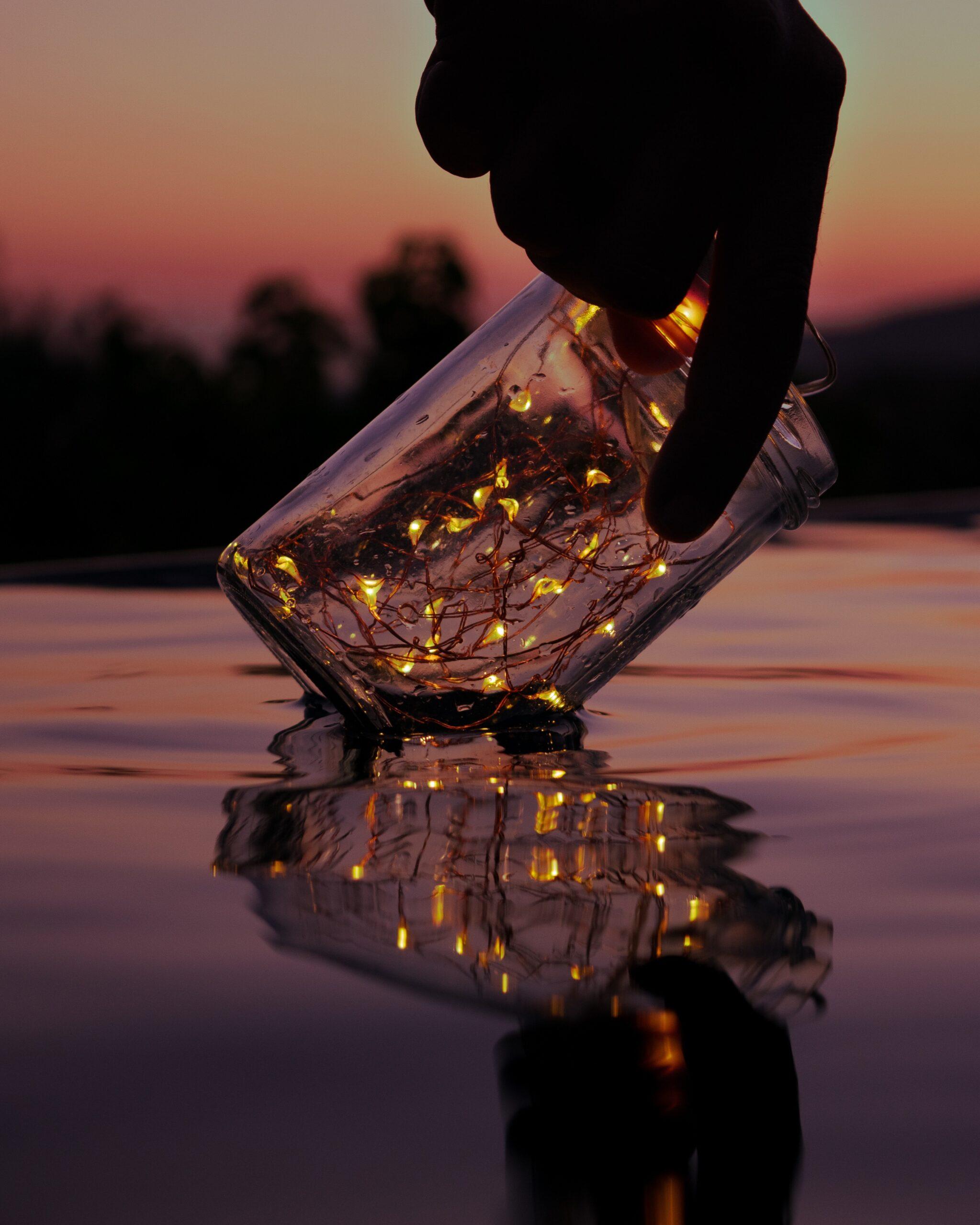 luigi-colonna-lights in a bottle held still over water-unsplash