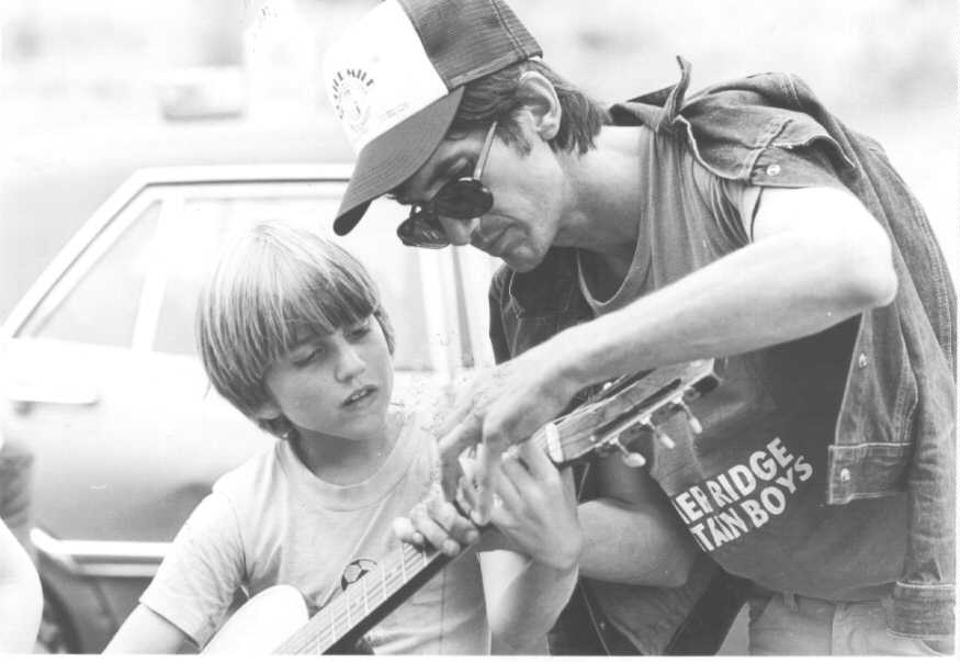 Townes Van Zandt with young boy showing how to pick chords