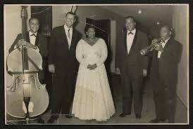 Photograph of bassist Bill Yancey (probable identification), pianist Paul Smith, Ella Fitzgerald, drummer Gus Johnson, and Roy Eldridge.