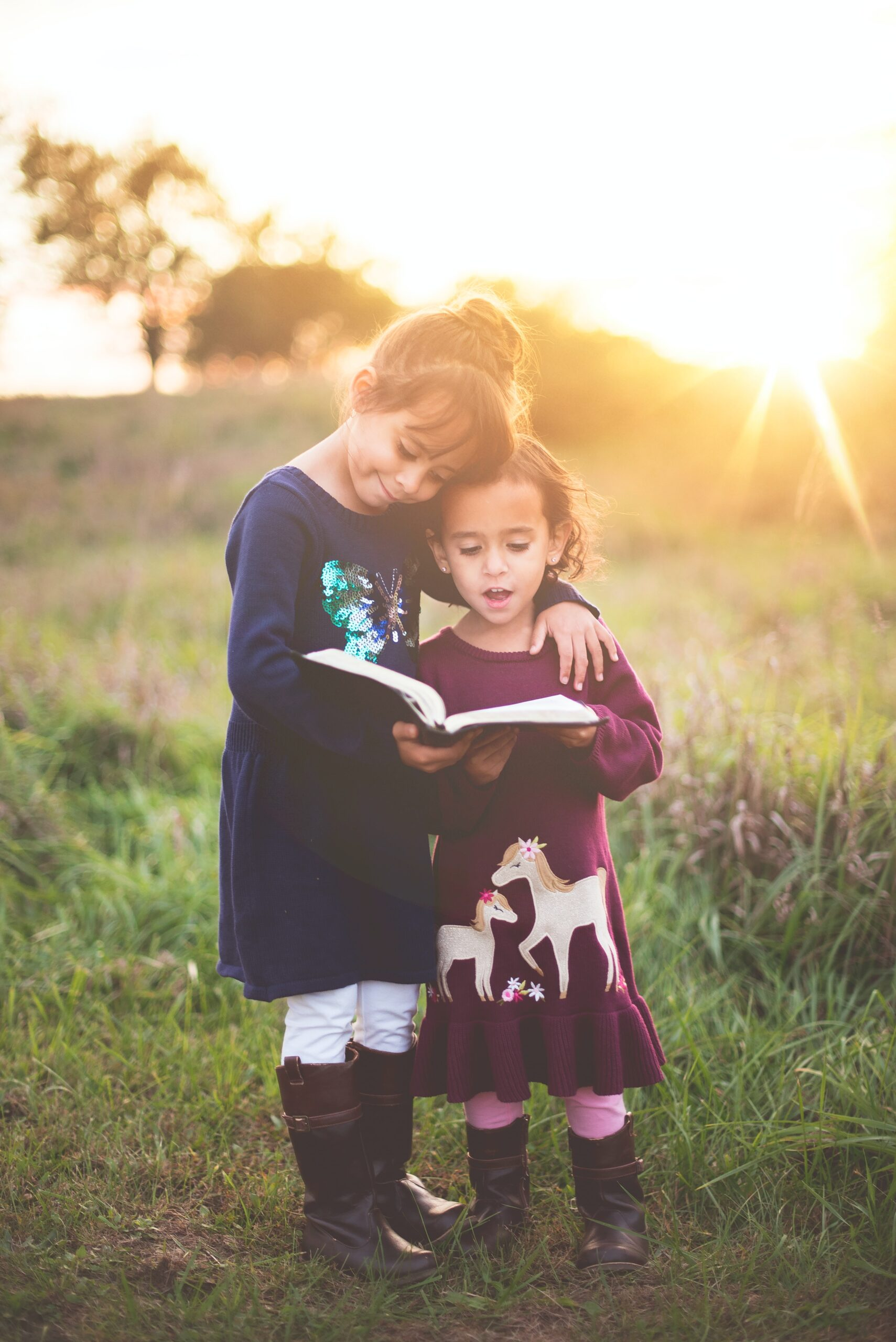 Sisters reading to each other in field by Ben White on Unsplash