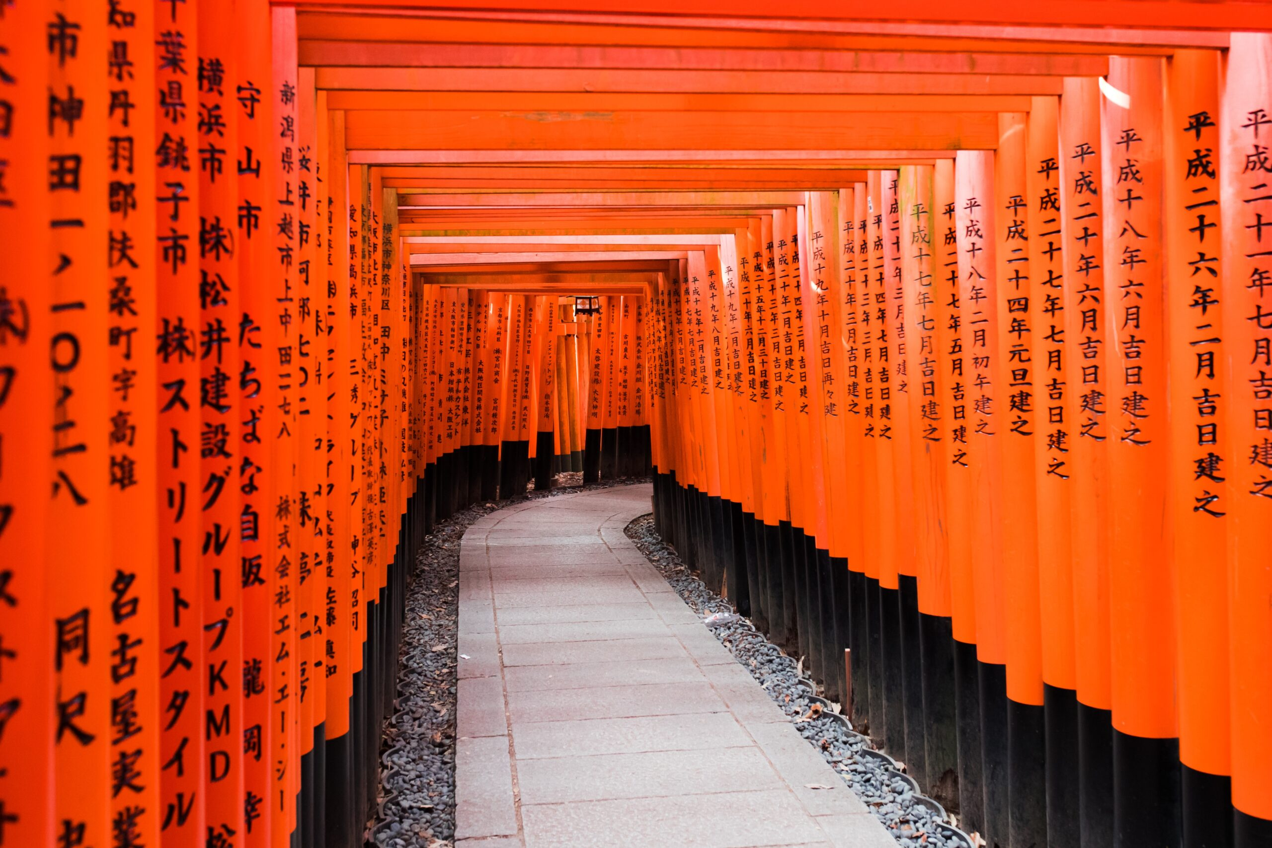 billy-pasco-Orange scroll walls with Japanese calligraphy forming walls with concrete paved path between-unsplash