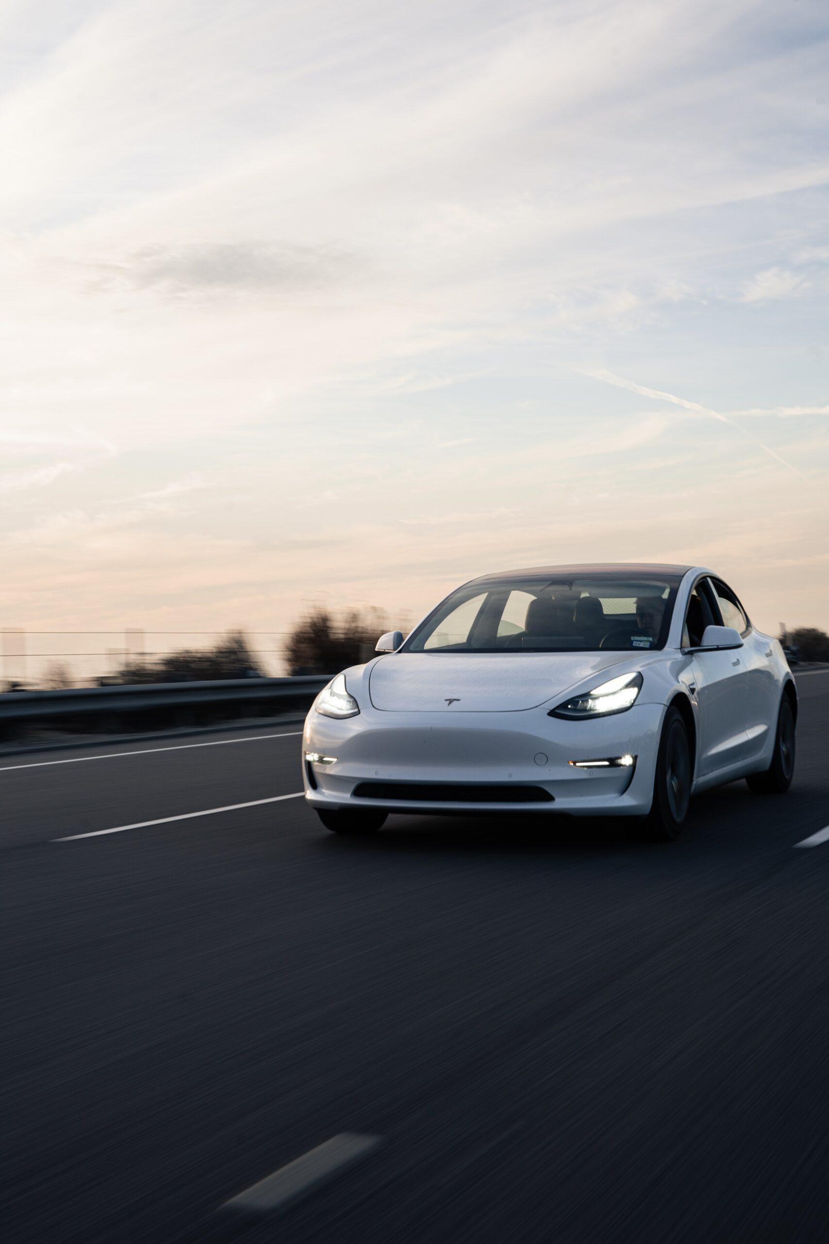 carter-baran-White Tesla Model 3 on highway-unsplash