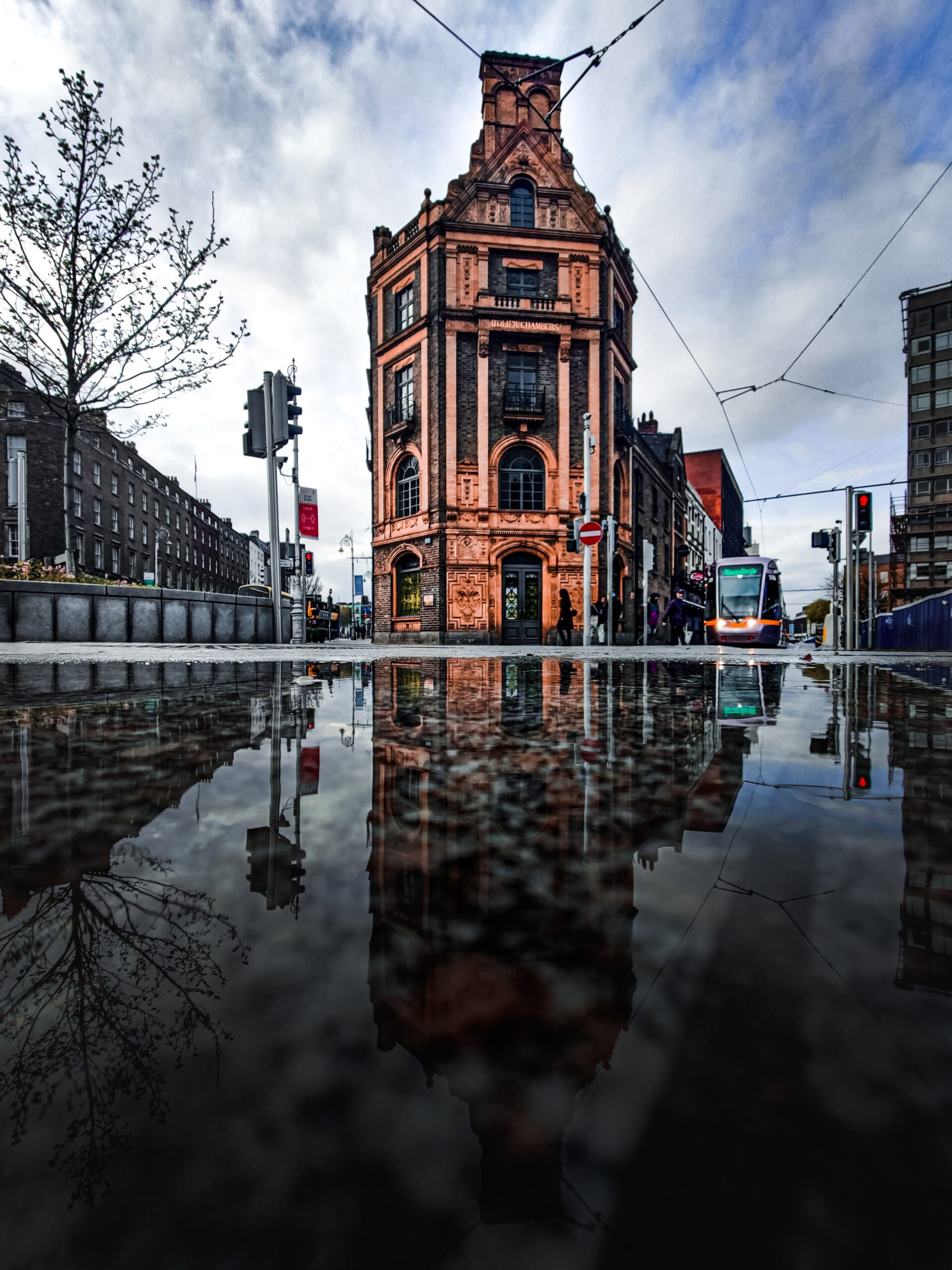 conor-luddy-Dublin city street level after rain with metro in frame-unsplash