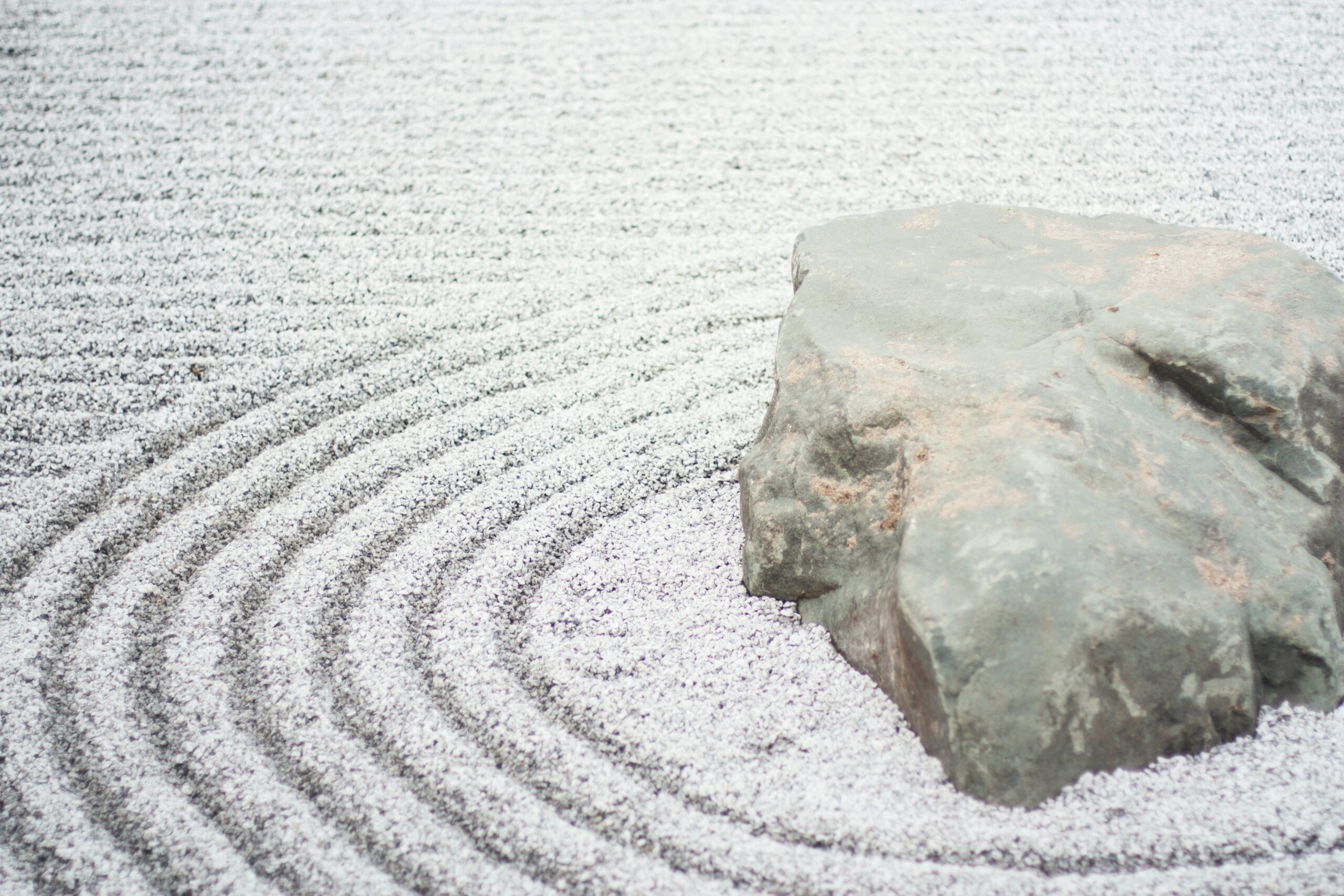 Zen Rock Garden with concentric circles in sand made by rake by Kari Shea on Unsplash
