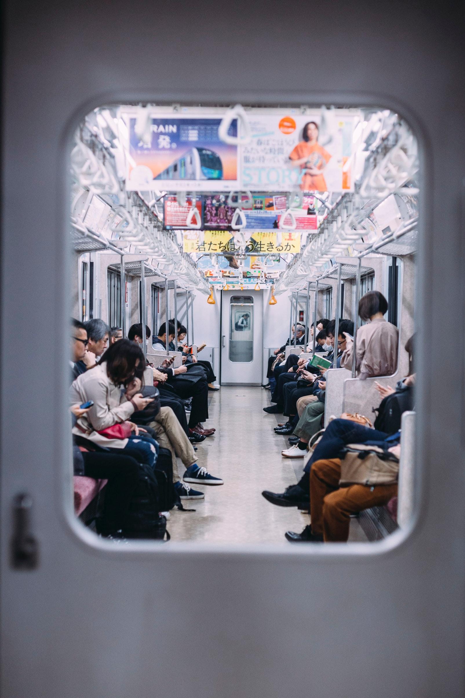 liam-burnett-blue--Tokyo Japan subway interior with commuters-unsplash