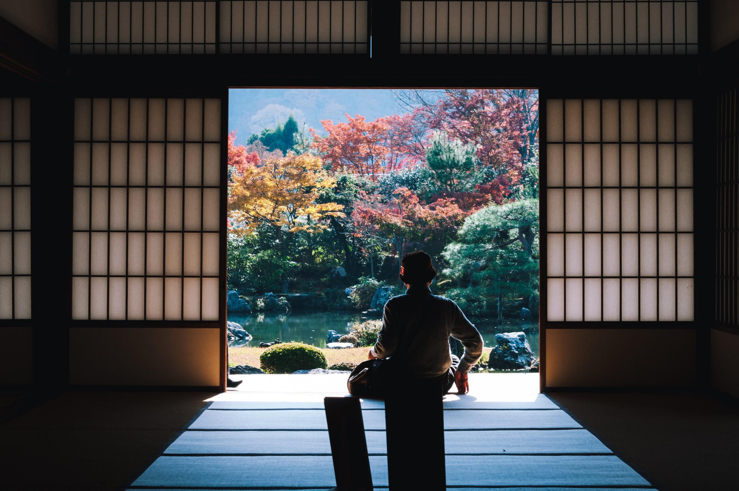masaaki-komori-Gentleman sitting in Tea house looking out over pond-unsplash