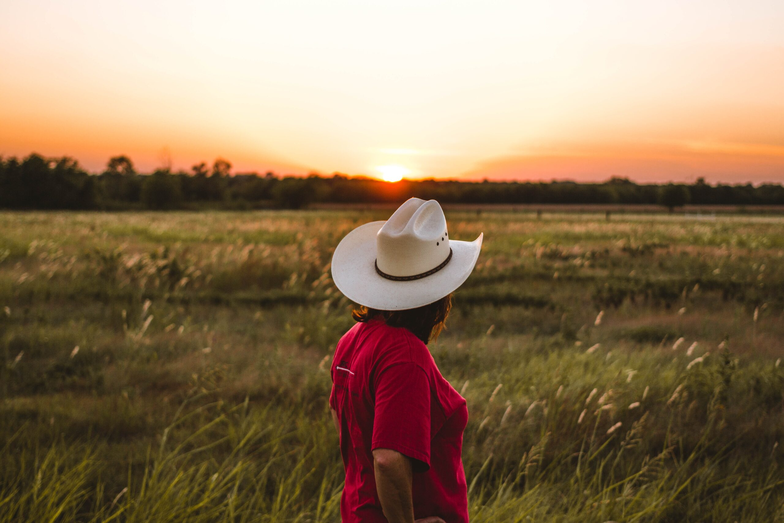justin-clark-cowgirl looking out over prarie sunset-unsplash