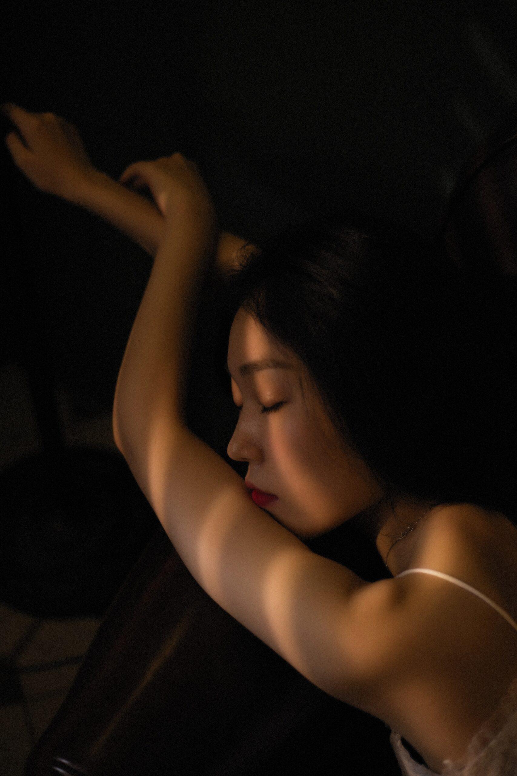 Woman sleeping on brown sheets