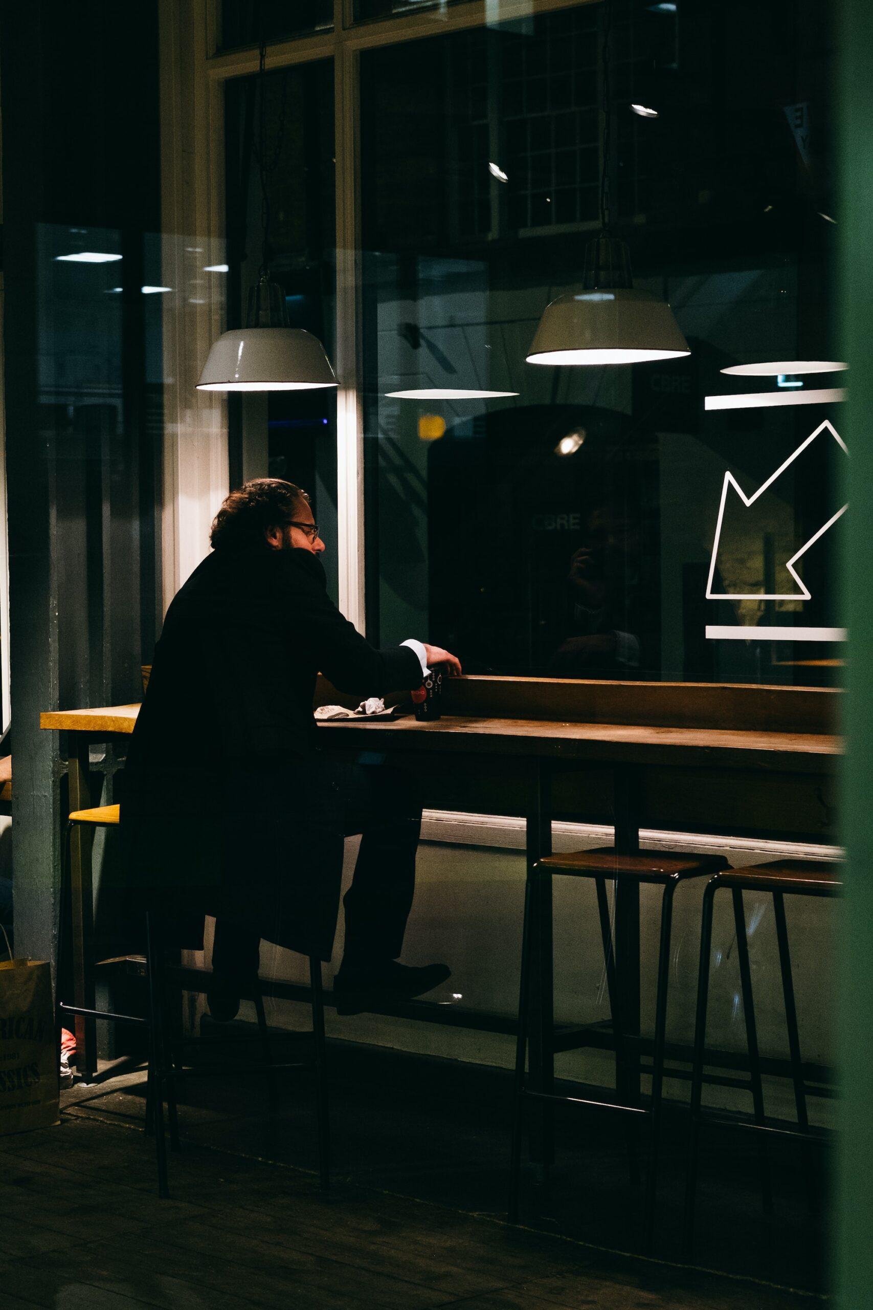 jay-clark-Man sitting in cafe late at night-unsplash